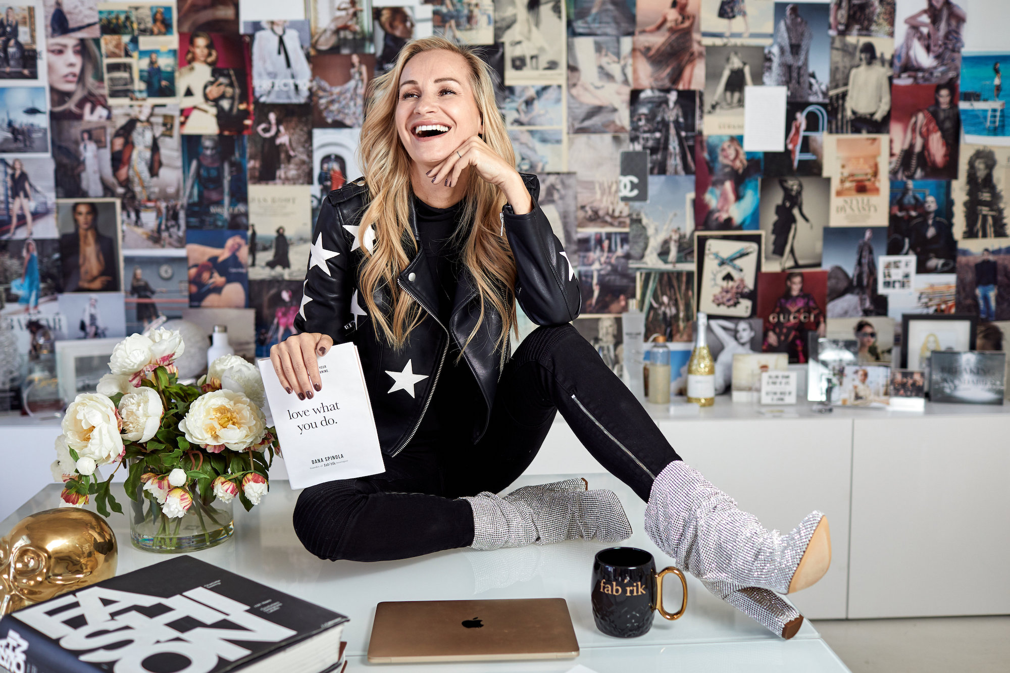 Dana Spinola, sitting on her desk in the fab'rik corporate office
